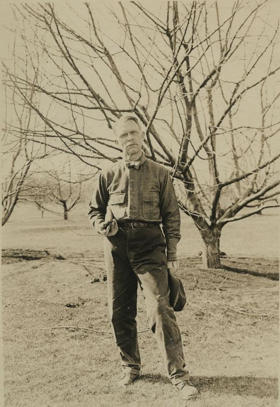Ray Stannard Baker standing next to some trees on his property
